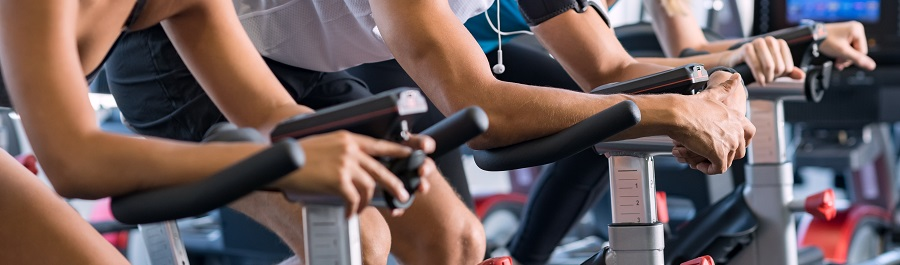 Young people talking and smiling while working out on an exercise bike in their home gym facility