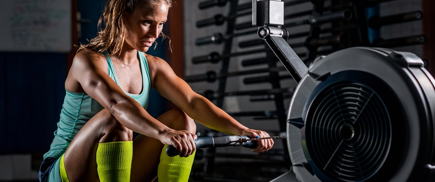 Woman athlete exercising on rowing machine at home