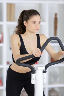 Young lady using fitness equipment in her home gym