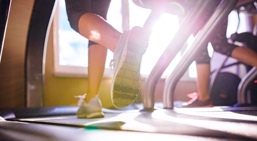 Close up of legs of two women running on treadmills in a gym, sunny day with top rated shoes