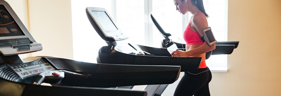 Beautiful young sportswoman with earphones and blank screen smartphone using treadmill and drinking water in gym
